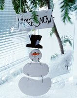 Wooden snowman with labelled sign hung from fir branch