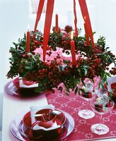 Christmas table set in red and white below Advent crown of berries and lit candles
