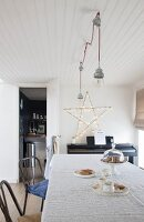 Large fairy-light star on wall in simple dining room