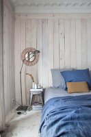 Bed with blue bed linen against white-stained board wall in bedroom