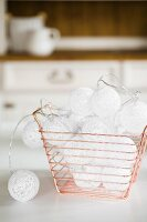 Fairy lights with white spherical shades in copper-wire baskets