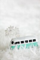 Miniature VW bus amongst pile of white fluffy rug