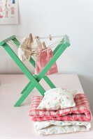 Dolls' clothes on green, wooden, doll's drying rack next to folded blankets and cushions for dolls' house