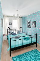 Metal bed and floral wallpaper in blue bedroom