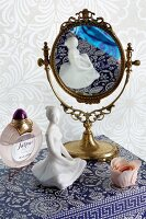 Feminine still-life arrangement of mirror, china figurine and perfume