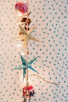 Paper stars and Christmas baubles hanging from fairy lights against polka-dot background