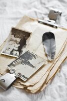 Feather and old photos on stack of vintage paper