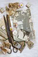 Vintage arrangement of daisies, vintage scissors, metal clips and old photos