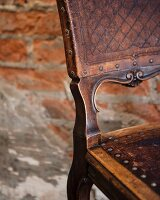 Antique wooden chair in front of brick wall (detail), Restaurant Charango, Cape Town, South Africa