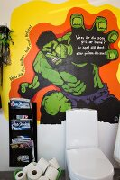 Toilet with cistern and magazine rack on wall with Incredible Hulk mural