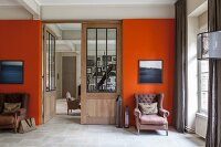 Two armchair below artworks on orange wall flanking door