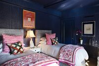 Twin beds with upholstered headboards and patterned scatter cushions in eclectic bedroom with dark blue walls