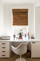 White desk and Tulip Chair below window with bamboo roller blind in retro interior
