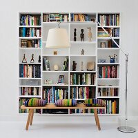 White bookcase in niche behind wooden bench and designer standard lamp