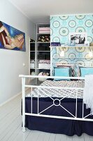 White metal double bed against partition wall with patterned wallpaper screening walk-in wardrobe