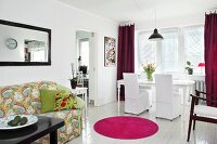 White, loose-covered chairs and dining table on white wooden floor, hot pink round rug and patterned sofa in open-plan living area