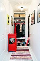 Cloakroom with shelving and coat pegs in niche, rag rug and red console cabinet