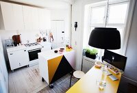 Half-height cabinet on castors in kitchen and computer monitor on yellow table in period apartment