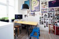 Dining and working area with yellow table, blue step-stool and collection of photos and framed posters on wall