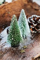 Miniature landscape made from Christmas tree ornaments and gold paper stars on bark