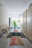 Chairs, cupboards and various rugs on marble-tiled floor in wide hallway
