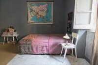Table lamp on white chair next to bed with ethnic bedspread and map decorating wall in bedroom