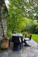 Black classic chairs and dining table on stone terrace outside Italian farmhouse
