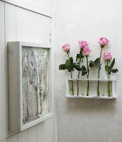 Roses in test tubes in wall bracket next to artwork