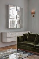 Glass coffee table, velvet sofa, white floating sideboard and mirrored wall-mounted cabinet in corner of living room