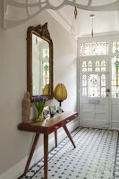 Retro console table below antique gilt-framed mirror in traditional hallway with Art-Nouveau stained glass panels in front door