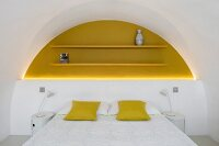 Yellow scatter cushions on double bed against half-height white wall below yellow-painted floating shelves in arched yellow niche with indirect lighting