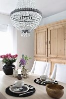 Table set for two below chandelier with glass pendants in rustic, elegant dining room
