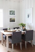 Dining area with grey upholstered chairs in rustic interior with white wood-clad walls