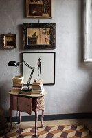Antique, fabric-covered bedside table below pictures on wall