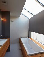 Elegant, minimalist, attic bathroom with shower area, bathtub and exotic-wood installations