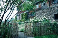 A stave fence with an open gate, white lilac bushes in front of an old country house with a natural stone and shingle facade