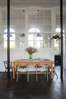 Dining table, black steel pillars and interior windows in loft apartment