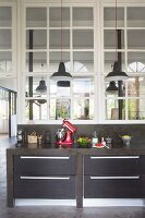 Black, concrete kitchen counter with drawers and kitchen utensils below interior windows in loft-style apartment