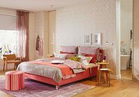 A feminine bedroom with a box spring bed in shades of red and gold patterned wallpaper