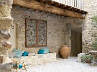 Stone-built bench with cushions under ornate window shutters in Mediterranean courtyard