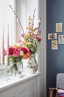 A bunch of different coloured roses in a glass vase and a bunch of flowers with carnations in a decorative vase