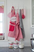 Red and white apron and tea towels hanging from vintage pegs with old-fashioned storage jars in foreground