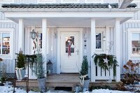 Festively decorated porch with wooden veranda in Scandinavian style