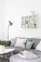 Grey corner sofa with scatter cushions below collection of vases in wall-mounted display case