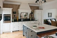 Island counter in white country-house kitchen with view into living area