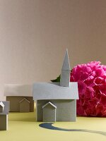 Paper models of church and house in front of pink hydrangea flower