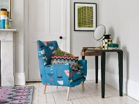 Retro chair with patterned upholstery and colourful scatter cushion next to console table