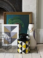 Still-life arrangement of retro vases, small wire house and picture in gilt frame