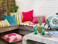 Row of colourful scatter cushions on terrace bench