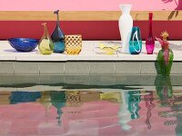 Collection of elegant vases on edge of pool reflected in water